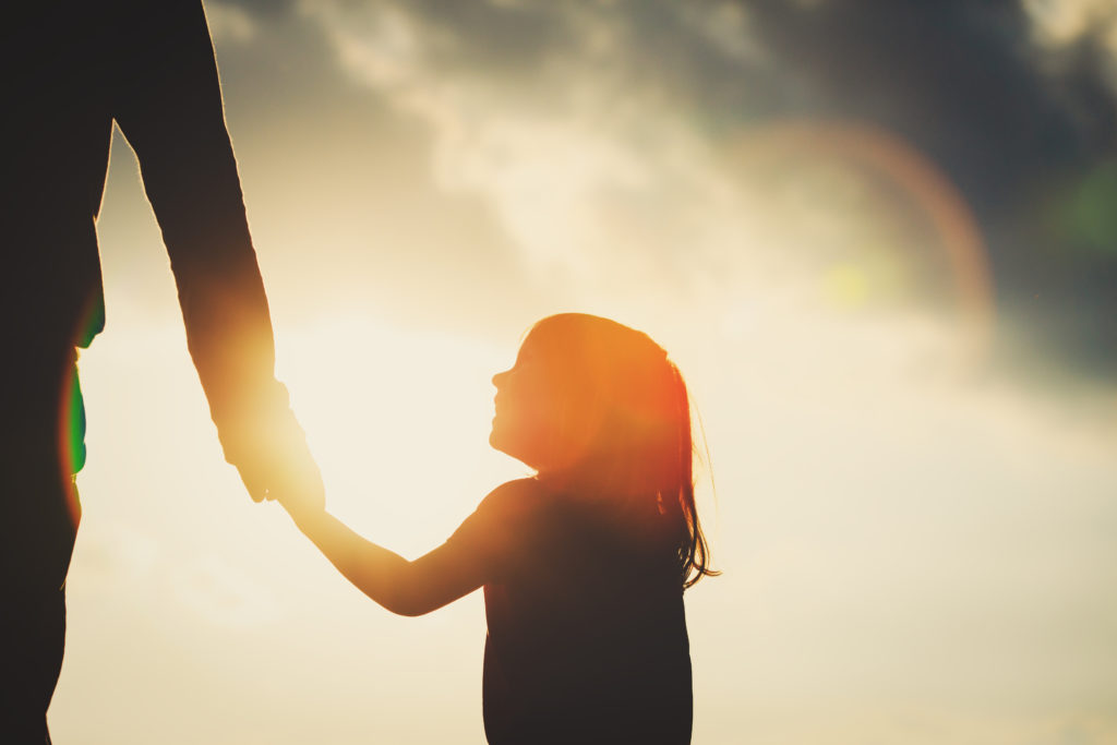 Silhouette of little girl holding parent hand at sunset. Parental alienation concept.