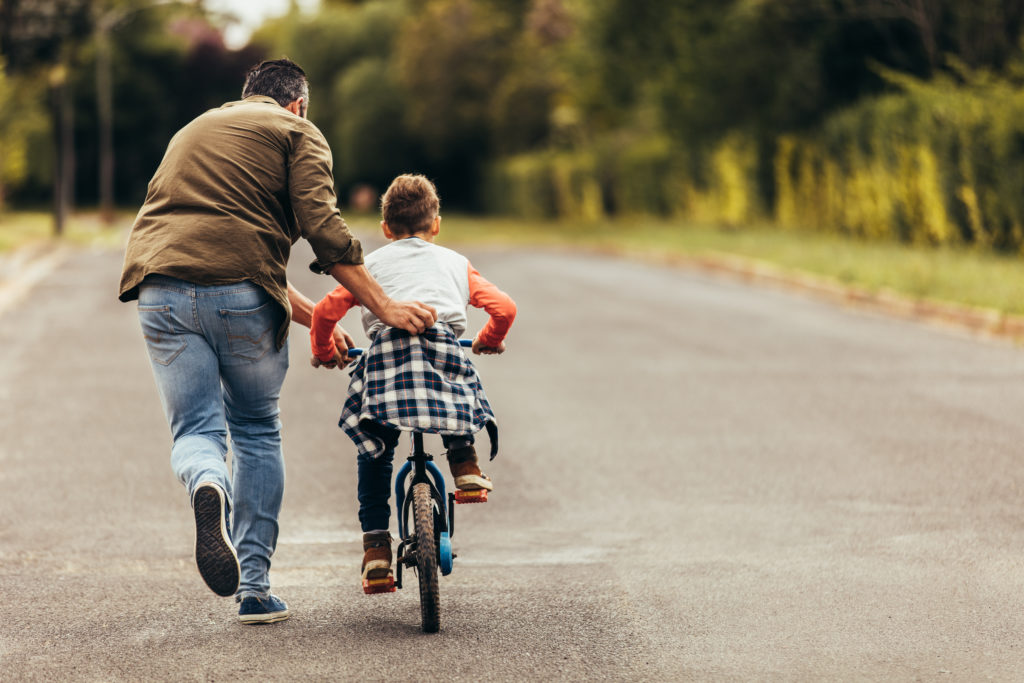 Modifying child support concept. Man helping his kid in learning to ride a bicycle